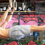 GymnasticBodies Athlete performs a front lever core exercise on gymnastic rings