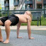 A GymnasticBodies desk worker table rocks his way to healthy shoulder extension.