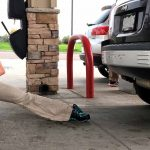 Female GymnasticBodies athlete stretching out tight muscles during her road trip.