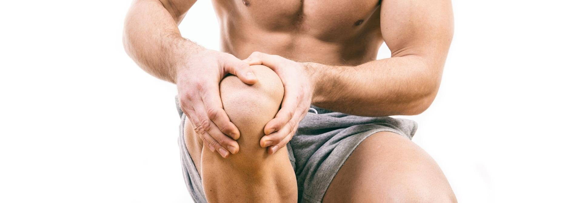 Athlete holds knee in pain because he didn't prehab them with GymnasticBodies progressions.