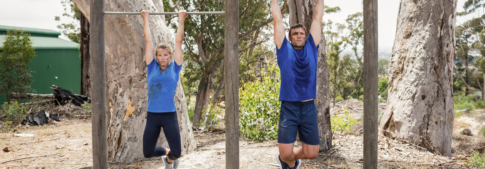 Couple hangs for their health on the pull-up bar.