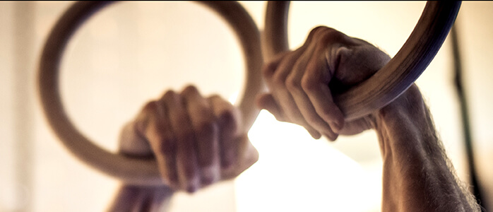 GymnasticBodies Athlete demonstrates a False Grip on Rings.