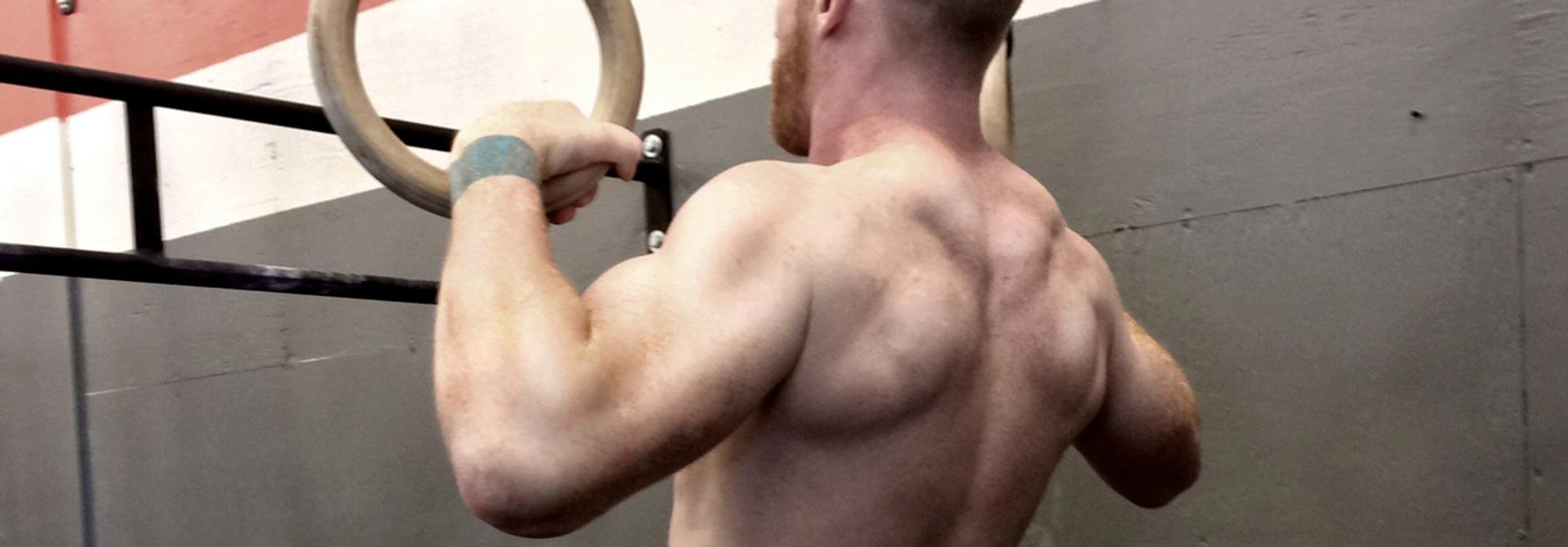 GymnasticBodies athlete shows off biceps that develop with advanced ring work.