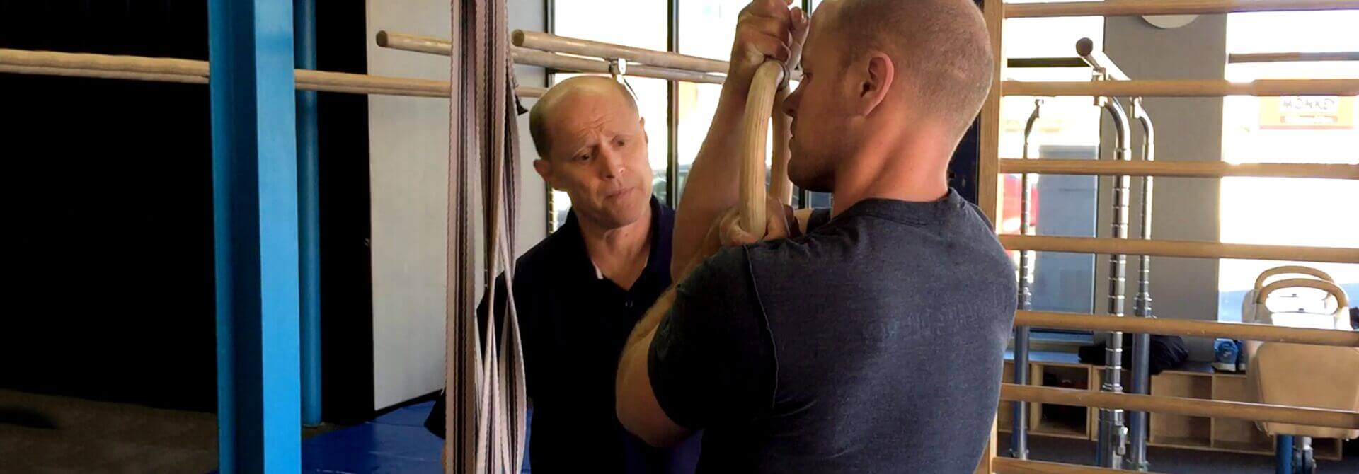 GymnasticBodies athlete Tim Ferriss works on false grip with Coach Christopher Sommer.
