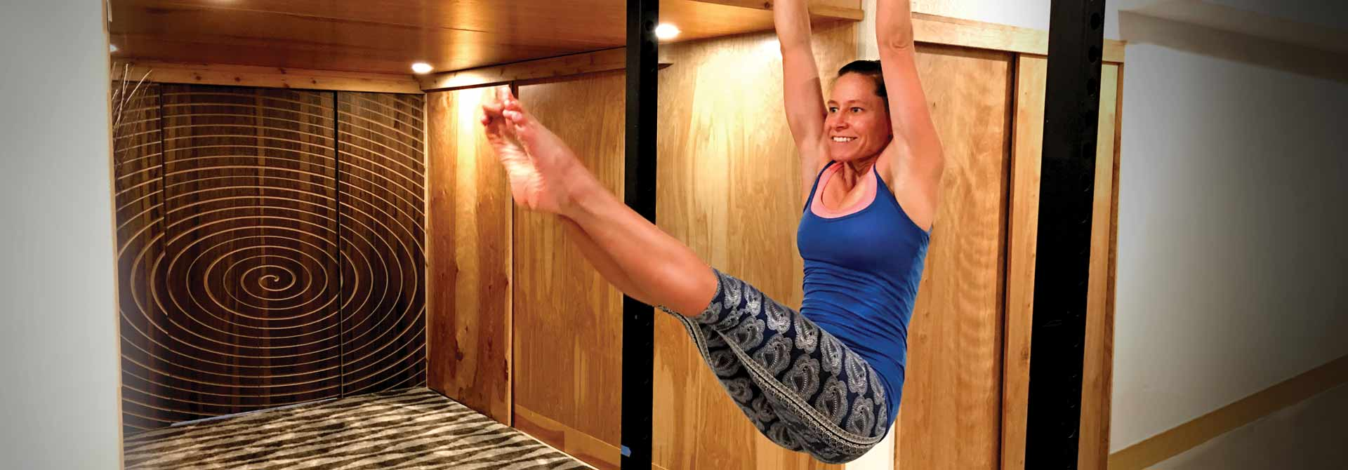 GymnasticBodies female athlete demonstrates core strength in a hanging Straddle-up.