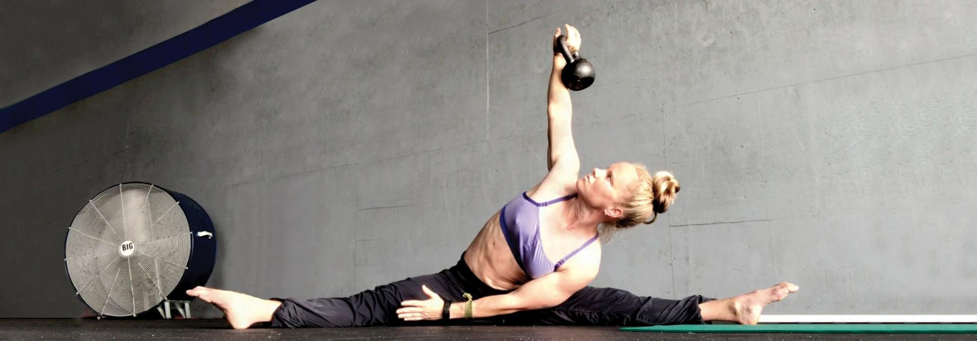GymnasticBodies female athlete demonstrates oblique strength with a weighted side pancake.