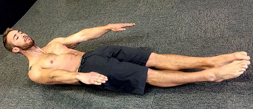 Christopher Sommer's athlete demonstrates body weight core exercise, the hollow body hold with hands to the sides.