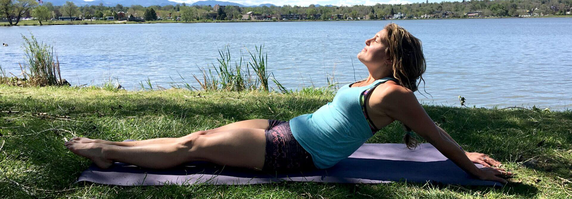 GymnasticBodies female athlete relaxes in the park while stretching her shoulders, with a shoulder extension stretch.