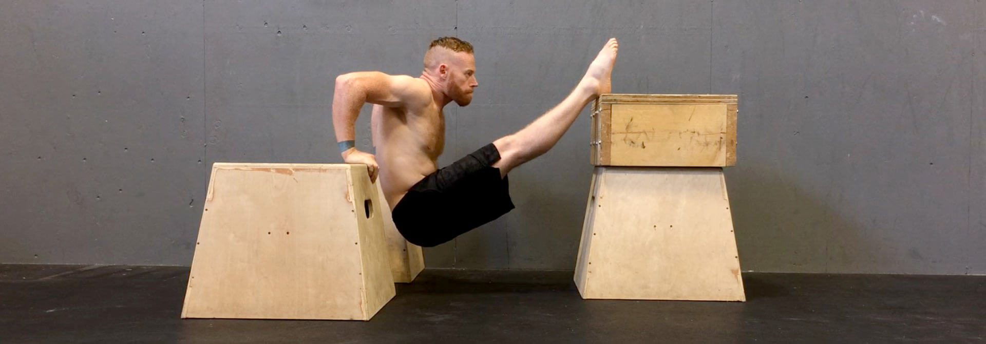 GymnasticBodies athlete demonstrates a muscle-up progression, box dips.