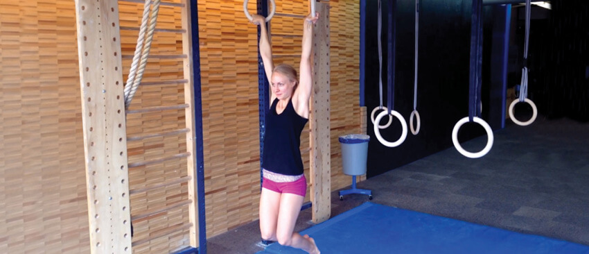 GymnasticBodies female athlete demonstrates a strong grip and mobile shoulders with a false grip dead hang.