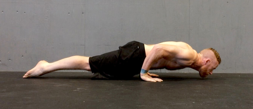GymnasticBodies athlete demonstrates a strong chest, back, and shoulders with a pseudo-planche push-up.