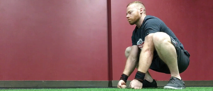 Christopher Sommer's ape stance opens up your hips and lower back, while also giving your calf muscles a nice stretch.