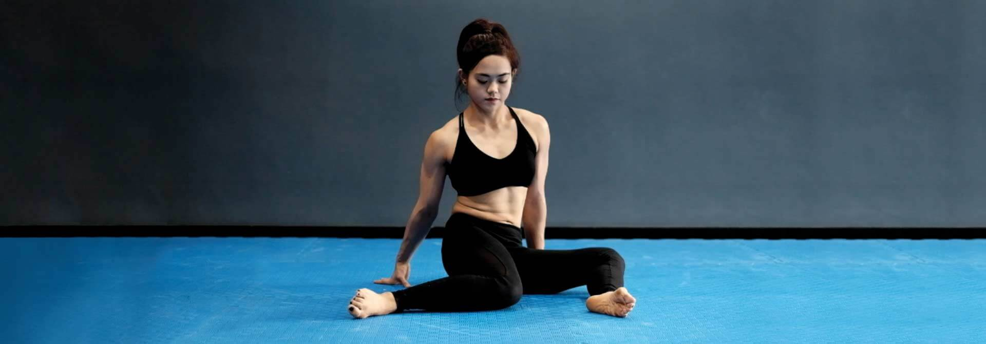 GymnasticBodies female athlete demonstrates hip swivels, an exercise that gently loosens the hip joints.