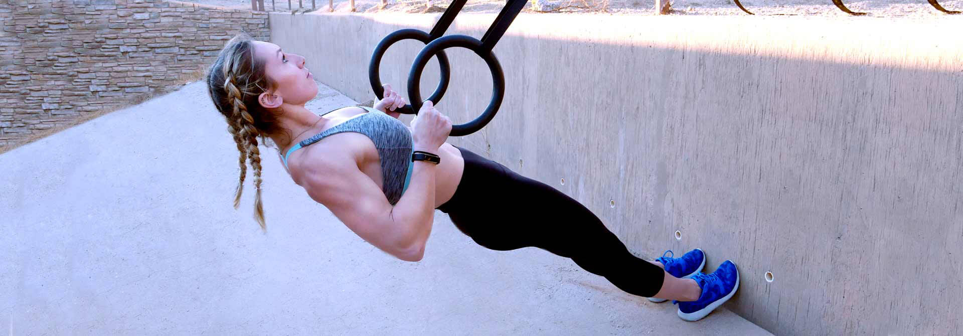 GymnasticBodies female athlete demonstrates a pull-up progression with rings.